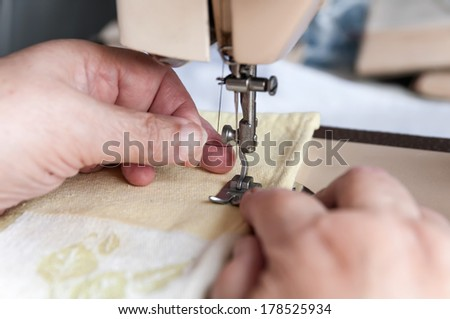 an elderly woman sticks it in a thread in the needle for sewing machine - stock photo