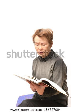 An elderly woman to reading the thick book