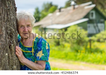 An elderly woman was leaning against a tree near the farmhouse. - stock photo