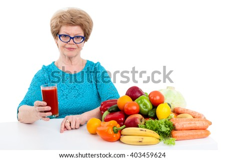 An elderly woman with glass of tomato juice in her hand sitting at table with fruits and vegetables, isolated on white background - stock photo