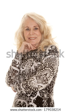 An elderly woman with her hand under her chin in her beautiful dress. - stock photo