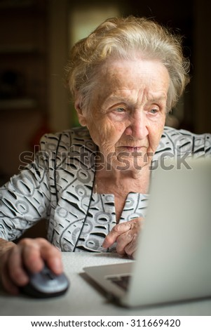 An elderly woman working on a laptop. Senior woman with computer. - stock photo