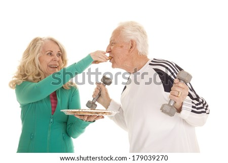 An elderly women giving her husband a bite of a cookie. - stock photo
