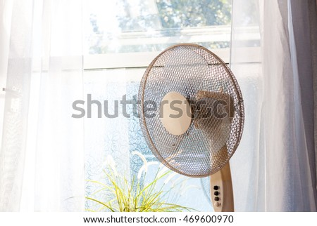 An electric fan in front of a bright window on a hot sunny day