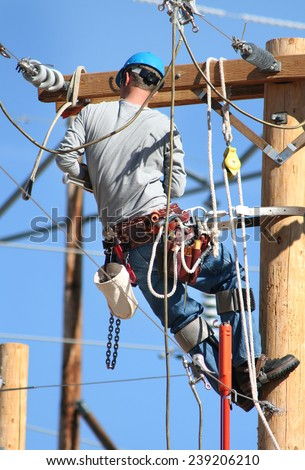 an electrical lineman working on lines - stock photo