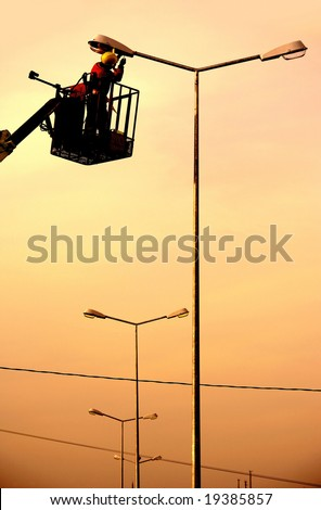 An electrical power utility worker in a bucket fixes the power line - stock photo