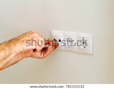 An electrician installing new electrical plugs using a screwdriver during the renovation of the house