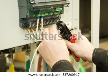 an electrician installs the electric meter
