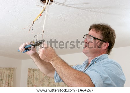 An electrician uses pliers to straighten and separate wires.  Work is being performed to code by a licensed master electrician.