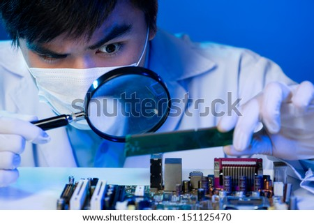 An electronic engineer analyzing the computer motherboard with the zoom on the foreground