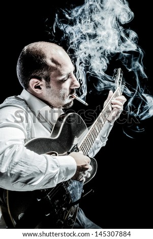an elegant and very focused musician playng an acoustic guitar and smoking - stock photo