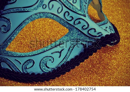an elegant blue and black carnival mask on a golden background - stock photo