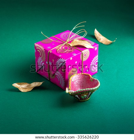An elegant bright gift box with Diwali lamp. An Indian festive gift. - stock photo