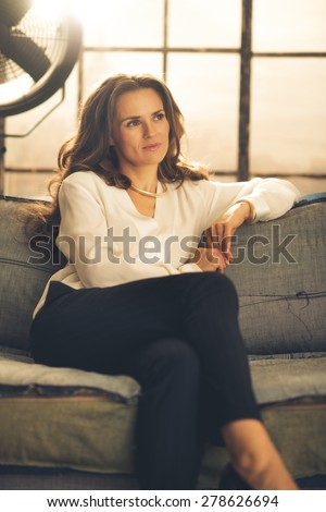An elegant brunette is sitting, legs crossed, on a sofa in a loft. Looking into the distance, she is smiling softly, and her hair is loose. In the background, light shines through a large window.