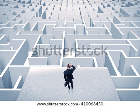 An elegant businessman standing on a square platform looking over infinite labyrinth concept - stock photo