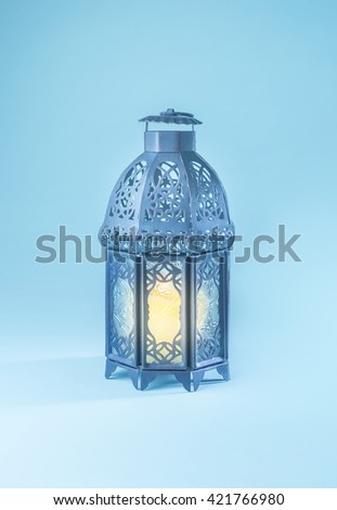 An elegant graphic Ramadan lantern on soft blue background. - stock photo