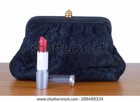 An elegant, lacy black clutch woman's evening bag laying on a wooden table, isolated on white. Red lipstick is opened. Concept of feminine glamour and party or celebration. Isolated on white. - stock photo