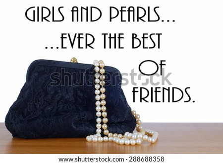 An elegant, lacy black clutch woman's evening bag laying on a wooden table, isolated on white. Two strings of pearls are spilling out of the bag.  Isolated on white. Removable text message - stock photo