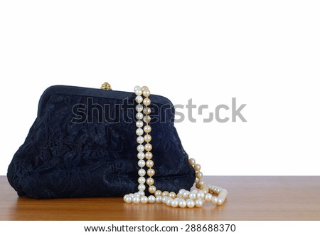 An elegant, lacy black clutch woman's evening bag laying on a wooden table, isolated on white. Two strings of pearls are spilling out of the bag.  Isolated on white. Copy space available. - stock photo
