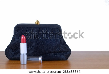 An elegant, lacy black clutch woman's evening bag laying on wooden table, isolated on white. Red lipstick is opened. Concept of feminine glamour and party or celebration. Isolated on white. Copyspace - stock photo