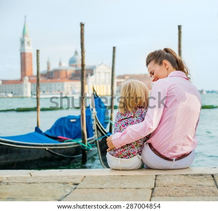 An elegant mother looks lovingly down at her daughter as she holds her close for a hug. They are happy, relaxed, and enjoying sitting by the water's edge, just spending time together. - stock photo