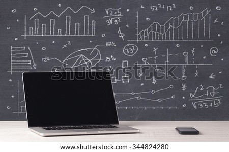 An elegant office desktop with portable laptop and drawn pie charts, graphs, numbers in the background concept - stock photo