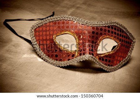 an elegant red carnival mask on a brown background - stock photo