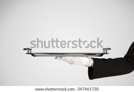 An elegant waiter business hand in white glove holding an empty plate with grey blank gradient background. - stock photo