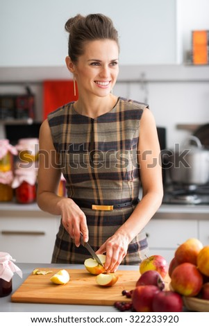 An elegant woman is standing in her kitchen, preparing apples to use to make applesauce and other fruit preserves. With a dash of cinnamon, the outcome will be delicious. - stock photo