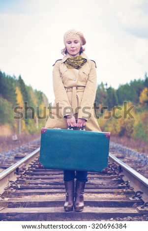 An elegant woman with a suitcase traveling by rail autumn day. - stock photo