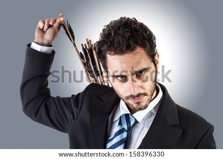 an elegant young businessman extracting an arrow from the quiver on his back - stock photo