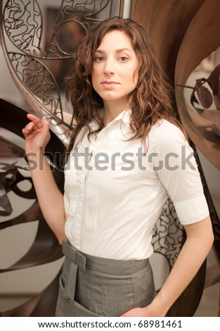 An elegant young woman in front of an modern iron sculpture - stock photo