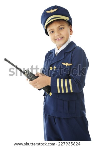 "An elementary ""airline pilot"" happily looking at the viewer while using his hand-held 2-way radio and navigator.  On a white background."