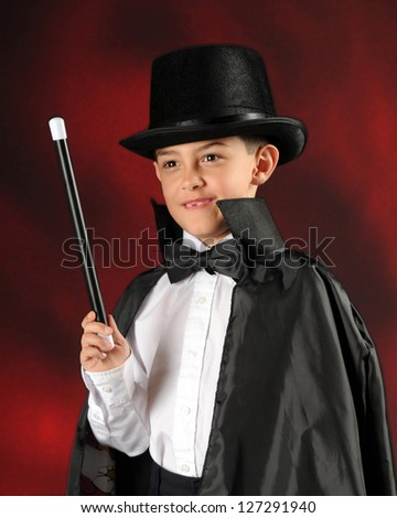 An elementary boy magician with cape, top hat, want and bow tie. - stock photo