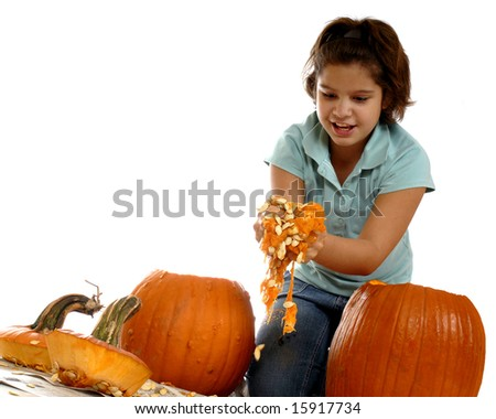 An elementary girl cleaning the goop out of her Halloween pumpkins before she can carve them.