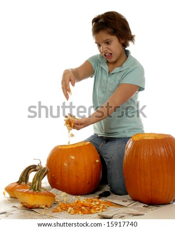 An elementary girl reacting to the yucky stuff she's scooping out of her pumpkin before she can carve it.