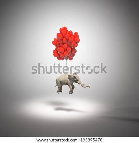 An elephant being lifted by balloons - stock photo