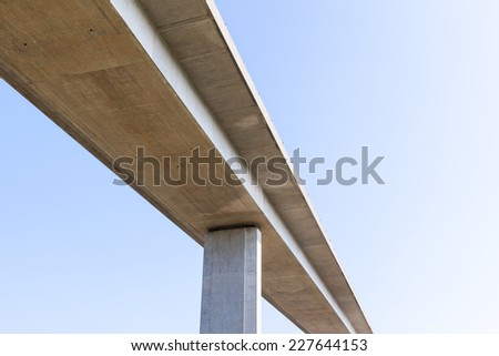 An elevated concrete road bridge seen from below. Supported by a single visible pillar. Blue sky background.