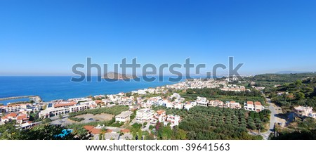 An elevated panoramic view of the greek resort of platanias with Chania city visible in the distance on the island of Crete.
