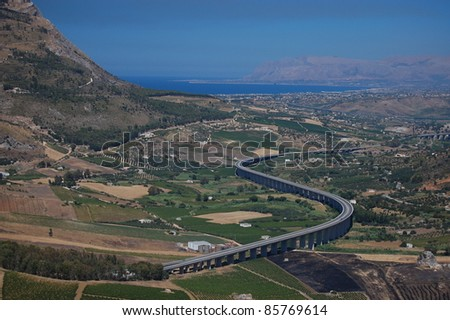 An elevated road snakes its way across the landscape of western Sicily