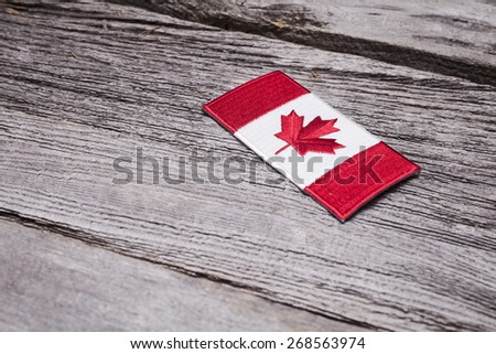 An embroidered Canadian flag patch sits on a rustic wooden background. - stock photo