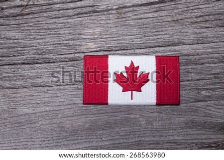 An embroidered Canadian flag patch sits on a rustic wooden background.