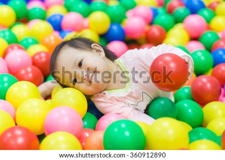An emotional face of smiling baby playing in the balls pool. Cute and happy girl. - stock photo