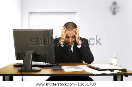 an employee stressed out holding his head looking at sales chart - stock photo