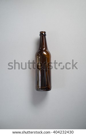 An empty beer bottle on grey background for recycling. - stock photo