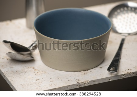An empty beige flat bottom soup bowl with blue interior, between a pair of spoons and a slotted spoon, all on a stone countertop.