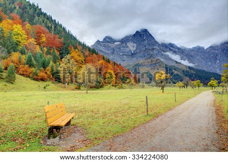 An empty bench by a hiking path through the meadow with maple trees on the mountainside ~ Beautiful autumn scenery of Karwendel Mountains in Eng, Hinterriss, Austria ~ European alps ~ - stock photo