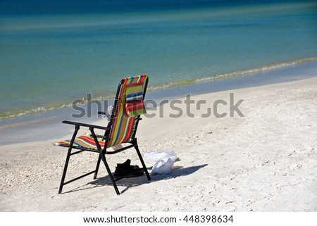 An Empty Bright Colored Beach Chair on the Beach - stock photo