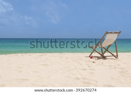 an empty chair in white sand in an exotic beach