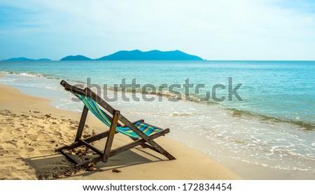 An empty chair on a sandy beach near the water  - stock photo